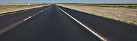 Light traffic travels Interstate 20 in flat rural agricultural land in west Texas with a railroad track paralleling.   panorama