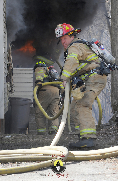 4/8/11 -- BRUNSWICK, Maine. A Brunswick Fireman hauls hoses towards the blazing entryway where the fire started on Friday afternoon at 18 Oak St in Brunswick. No one was hurt - but it spread quickly from the entryway on the right side, consuming nearly the entire building in minutes. Photo by Roger S. Duncan.
