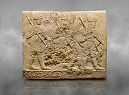 Hittite sculpted orthostats of Long Wall Limestone, Karkamıs, (Kargamıs), Carchemish (Karkemish), 900-700 BC. Anatolian Civilisations Museum, Ankara, Turkey<br /> <br /> Soldiers. Figure of three helmeted warriors. They have their shield in their back and their spear in their hand. The prisoners in their front are depicted as small. The lower part of the orthostat is decorated with wring / braiding motifs.<br /> <br /> On a grey art background. .<br /> <br /> If you prefer to buy from our ALAMY STOCK LIBRARY page at https://www.alamy.com/portfolio/paul-williams-funkystock/hittite-art-antiquities.html  - Type  Karkamıs in LOWER SEARCH WITHIN GALLERY box. Refine search by adding background colour, place, museum etc.<br /> <br /> Visit our HITTITE PHOTO COLLECTIONS for more photos to download or buy as wall art prints https://funkystock.photoshelter.com/gallery-collection/The-Hittites-Art-Artefacts-Antiquities-Historic-Sites-Pictures-Images-of/C0000NUBSMhSc3Oo