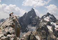 """Sam Coffin gingerly tags the 12.325-foot summit of Teewinot Mountain in Grand Teton National Park. The mountain, the northern-most spire of peaks known as the Cathedral Group, is named with the Shoshone Indian word meaning """"many pinnacles."""" The Teton Glacier is visible below the Grand's North Face."""