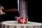 A mallet is used to smash an apple.