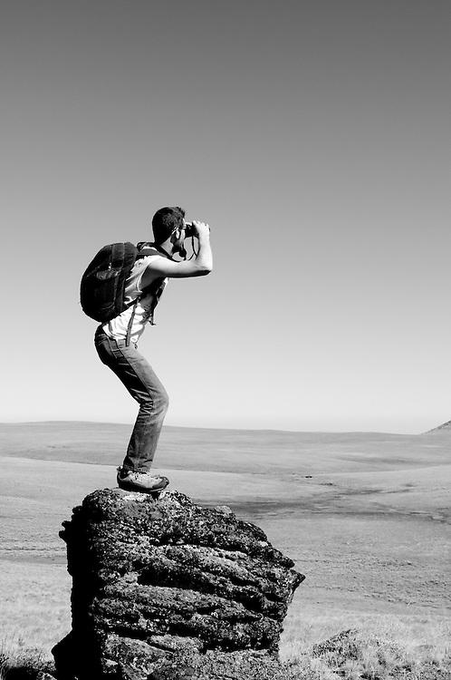 My friend Ryan standing and using binoculars on a column of basalt rock on Hart Mountain National Wildlife Refuge, Southeastern Oregon