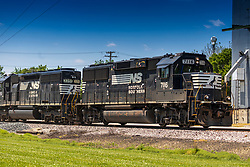Norfolk and Southern locomotives 7116 and 3351 pull rolling stock through the crossing and past the grain elevator in Arrowsmith Illinois.