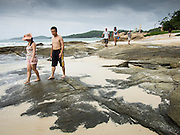 30 JULY 2013 - KOH SAMET, RAYONG, THAILAND: Tourists walk along Ao Phia beach on Koh Samet island. This part of the island was not impacted by the oil spill that fouled the west side of the island. About 50,000 liters of crude oil poured out of a pipeline in the Gulf of Thailand over the weekend authorities said. The oil made landfall on the white sand beaches of Ao Prao, on Koh Samet, a popular tourists destination in Rayong province about 2.5 hours southeast of Bangkok. Workers from PTT Global, owner of the pipeline, and up to 500 Thai military personnel are cleaning up the beaches. Tourists staying near the spill, which fouled Ao Prao beach, were evacuated to hotels on the east side of the island, which was not impacted by the spill. PTT Global Chemical Pcl is part of state-controlled PTT Pcl, Thailand's biggest energy firm.      PHOTO BY JACK KURTZ
