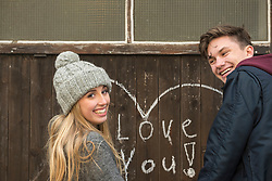 Young couple standing near wall on which heart is drawn and love you written on a wooden wall, Munich, Bavaria, Germany