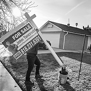 A contractor places the For Sale sign in Erin's yard as her home is put up for sale.