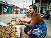 01 JUNE 2015 - KULAI, JOHORE, MALAYSIA:  A Rohingya refugee woman sells betel nut on a street in a Rohingya community in Kulai, Malaysia. This informal work is the only work she can find. The UN says the Rohingya, a Muslim minority in western Myanmar, are the most persecuted ethnic minority in the world. The government of Myanmar insists the Rohingya are illegal immigrants from Bangladesh and has refused to grant them citizenship. Most of the Rohingya in Myanmar have been confined to Internal Displaced Persons camp in Rakhine state, bordering Bangladesh. Thousands of Rohingya have fled Myanmar and settled in Malaysia. Most fled on small fishing trawlers. There are about 1,500 Rohingya in the town of Kulai, in the Malaysian state of Johore. Only about 500 of them have been granted official refugee status by the UN High Commissioner for Refugees. The rest live under the radar, relying on gifts from their community and taking menial jobs to make ends meet. They face harassment from Malaysian police who, the Rohingya say, extort bribes from them.       PHOTO BY JACK KURTZ