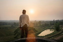 Rear view of a young man standing on mountain and looking at view during sunset, Laos