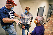 """22 SEPTEMBER 2020 - DUNLAP, IOWA: Congressional candidate J.D. SCHOLTEN (center) talks to JON SCHABEN, (left) a co-owner of Dunlap Livestock Auction, about farm policy. Scholten, a Democrat from Sioux City, Iowa, ran against incumbent CongressmanSteve King (R-4th District Iowa) in 2018 and came within a few percentage points of upsetting the long serving conservative. King lost to Randy Feenstra, a Republican challenger, in the 2020 primary and Scholten is running against Feenstra in the 2020 general election on November 3. Iowa's 4th district, centered in the agricultural and sparsely populated northwest corner of the state, is the largest congressional district in Iowa and encompasses about ⅓ of the state of Iowa. Scholten is on his """"Every Town Tour 2020."""" He is visiting all 375 towns in the 39 counties in the district.     PHOTO BY JACK KURTZ"""