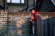 A cheeky young boy climbs over a back yard gate armed with a homemade bow and arrow in a back street in Liverpool, England. His homemade toy is the antithesis of what a wealthy lad might wish for in 21st century Britain when gadgets were all a kid wants and games outside have become rare and uncool. But this is still the early 1990s in times of recession when a make do and mend philosophy means families improvise with what they have and wealth is out of reach for many.