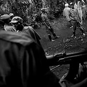 """Congolese Tutsi rebels from CNDP (Congré National pour la Defense du Peuple) gathered along with village children after their morning drill in Bunagana in 2008, one of their strongholds bordering Uganda. CNDP spokesperson in Bunagana claimed that their """"soldiers"""" were highly trained, and the group is listed in the lowest pyramid of committing sexual violence in the UN statistics."""
