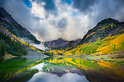 "The Maroon Bells are two peaks in the Elk Mountains, Maroon Peak and North Maroon Peak, separated by about a third of a mile. The mountains are about 12 miles southwest of Aspen. Both peaks are fourteeners. Maroon Peak, at 14,156 feet, is the 27th highest peak in Colorado; North Maroon Peak, at 14,014 feet, is the 50th highest. The view of the Maroon Bells to the southwest from the Maroon Creek valley is one of the most famous scenes in Colorado, and is reputed to be the ""most-photographed spot in Colorado"" and one of Colorado's premier scenic overlooks. The peaks are located in the Maroon Bells-Snowmass Wilderness of White River National Forest.<br /> <br /> A US Forest Service sign on the access trail refers to these mountains as ""The Deadly Bells"" and warns would-be climbers of ""downsloping, loose, rotten and unstable"" rock that ""kills without warning"". Unlike other mountains in the Rockies that are composed of granite and limestone, the Bells are composed of metamorphic sedimentary mudstone that has hardened into rock over millions of years. Mudstone is weak and fractures readily, giving rise to dangerously loose rock along almost any route. The mudstone is responsible for the Bells' distinctive maroon color. The Bells got their ""deadly"" name in 1965 when eight people died in five separate accidents.<br /> <br /> Maroon Lake (9,580') occupies a basin that was sculpted by Ice-Age glaciers and later dammed by landslide and rockfall debris from the steep slopes above the valley floor."