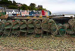 View of lobster pots and colourful buildings along waterfront at Tobermory harbour on Mull, Argyll & Bute, Scotland, UK
