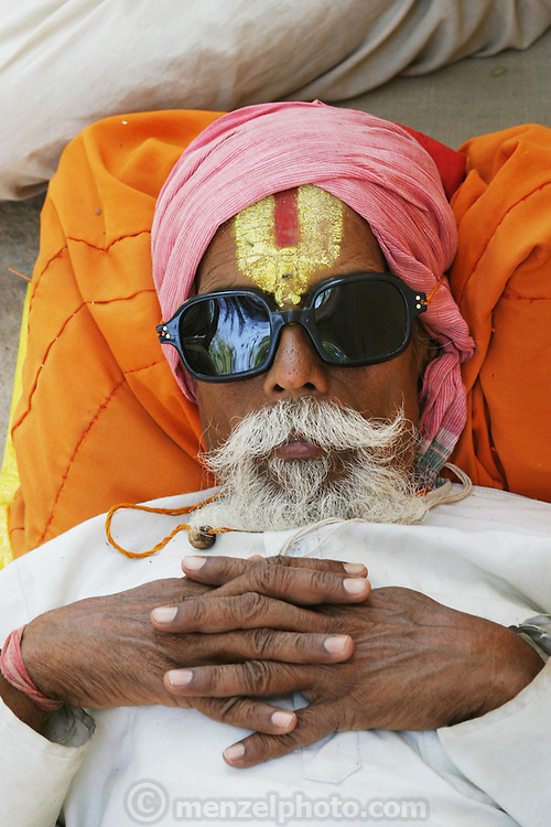 A pilgrim relaxing during the Kumbh Mela festival, Ujjain, Madhya Pradesh, India. The Kumbh Mela festival is a sacred Hindu pilgrimage held 4 times every 12 years, cycling between the cities of Allahabad, Nasik, Ujjain and Hardiwar. Kumbh Mela is one of the largest religious festivals on earth, attracting millions from all over India and the world. Past Melas have attracted up to 70 million visitors.