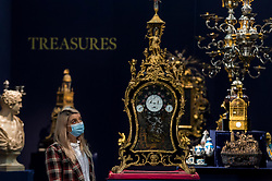 """© Licensed to London News Pictures. 07/12/2020. LONDON, UK. A staff member poses with """"A George III monumental gilt-mounted ebony quarter striking musical automaton clock for the Chinese market, English"""", circa 1780, (Est. £200k-300k). Preview of Sotheby's upcoming Christmas Sale Series of Old Masters and Treasures - paintings and objects spanning 800 Years.  The sales will be at Sotheby's New Bond Street gallery.  Photo credit: Stephen Chung/LNP"""