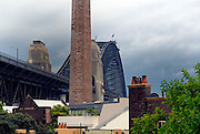 Looking across The Rocks' rooftops to the Sydney Harbour Bridge and an approaching storm. The Rocks, Sydney, Australia