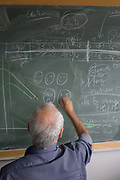 Portrait of mathematician and Risk guru, Professor Sir David Spiegelhalter with blackboard workings of probability, at the Centre for Mathematical Sciences at the University of Cambridge. Writing smilies on his blackboard, Spiegelhalter illustrates his theories about risk.  Sir David John Spiegelhalter (1953), OBE FRS, is a British statistician. In 2007 he was elected Winton Professor of the Public Understanding of Risk in the Statistical Laboratory, University of Cambridge and a Fellow of Churchill College, Cambridge. From the chapter entitled 'Possible Futures' and from the book 'Risk Wise: Nine Everyday Adventures' by Polly Morland (Allianz, The School of Life, Profile Books, 2015).