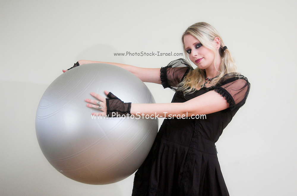 A young female model in her 20s wearing Lolita style clothes and high black boots playing with a ball