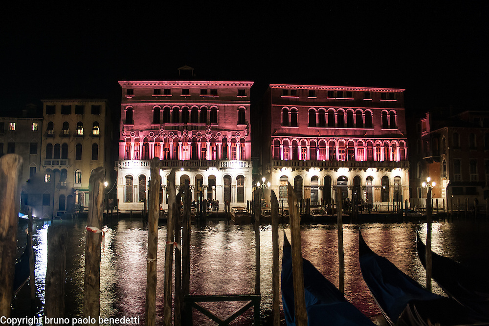 pink facade and gondolas on a channel in the night in Venice