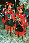 Andean mountain girls dress in traditional red ponchos in the Cordillera Urubamba, Andes highlands, Peru, South America. The moderately strenuous trek from Lares to Patacancha (near Ollantaytambo) traverses rugged, little-visited country in the Cordillera Urubamba across passes at 13,800 and 14,200 feet elevation. A five hour bus ride from Cuzco reaches Lares, where you can soak in developed hot spring pools. Llamas and horses carried our loads for two nights of camping at 12,500 feet elevation.