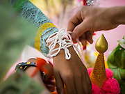 "05 APRIL 2015 - CHIANG MAI, CHIANG MAI, THAILAND: A layperson ties a string on the wrist of a Buddhist novice, a traditional Buddhist way of making merit, during the second day of the three day long Poi Song Long Festival in Chiang Mai. The Poi Sang Long Festival (also called Poy Sang Long) is an ordination ceremony for Tai (also and commonly called Shan, though they prefer Tai) boys in the Shan State of Myanmar (Burma) and in Shan communities in western Thailand. Most Tai boys go into the monastery as novice monks at some point between the ages of seven and fourteen. This year seven boys were ordained at the Poi Sang Long ceremony at Wat Pa Pao in Chiang Mai. Poy Song Long is Tai (Shan) for ""Festival of the Jewel (or Crystal) Sons.    PHOTO BY JACK KURTZ"