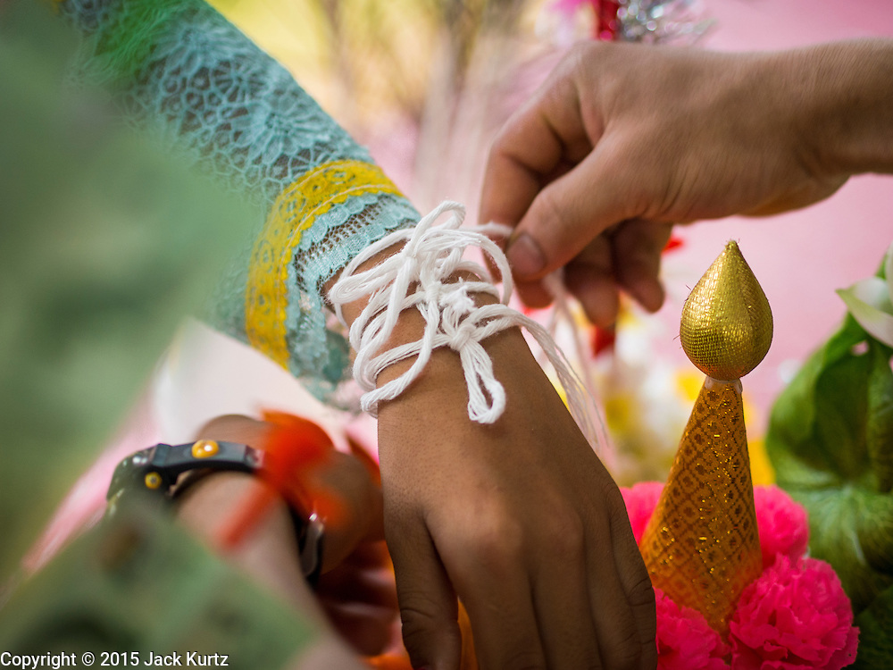 """05 APRIL 2015 - CHIANG MAI, CHIANG MAI, THAILAND: A layperson ties a string on the wrist of a Buddhist novice, a traditional Buddhist way of making merit, during the second day of the three day long Poi Song Long Festival in Chiang Mai. The Poi Sang Long Festival (also called Poy Sang Long) is an ordination ceremony for Tai (also and commonly called Shan, though they prefer Tai) boys in the Shan State of Myanmar (Burma) and in Shan communities in western Thailand. Most Tai boys go into the monastery as novice monks at some point between the ages of seven and fourteen. This year seven boys were ordained at the Poi Sang Long ceremony at Wat Pa Pao in Chiang Mai. Poy Song Long is Tai (Shan) for """"Festival of the Jewel (or Crystal) Sons.    PHOTO BY JACK KURTZ"""