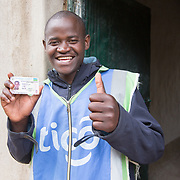 CAPTION: Jean Claude shows off his prized motorcycle driver's license. These licenses are notoriously difficult to get in Rwanda, and securing one brought down the final barrier to becoming a motorcycle taxi driver. He feels lucky to have heard about the Graduation Programme at a community meeting, and to have been selected among the first cohort of participants. He knew he would be good at investing what he'd be given wisely, and was excited to have the opportunity to work towards securing a better future for himself and his sister. From the time he was a young boy, Jean Claude was fascinated with the idea of becoming a car driver. He understood that a long road lay between him and this goal, so decided to break it up, first seeking to ride a bicycle taxi, then save towards buying a motorcycle to enable to earn more, and finally a car. LOCATION: Kabuga Village, Gafumba Cell, Rusatira Sector, Huye District, South Province, Rwanda. INDIVIDUAL(S) PHOTOGRAPHED: Jean Claude Minani.
