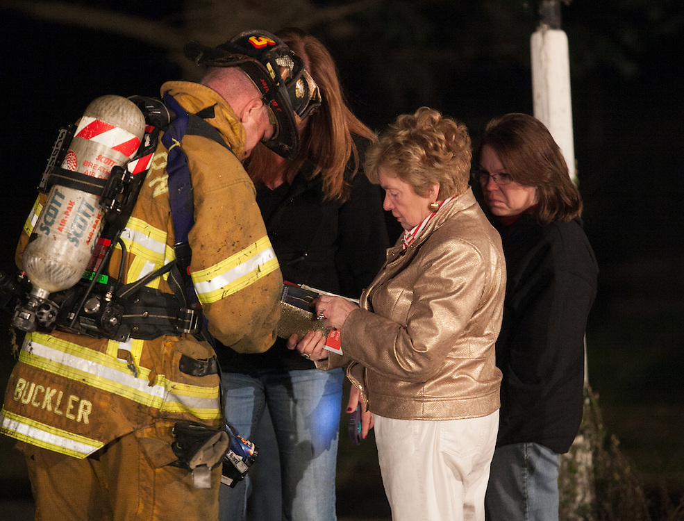 Sherborn, MA 04/11/2013.Lt. Josh Buckler of the Sherborn Fire Department hands over valuable items that were saved to the home's owner after a 3 alarm fire broke out at 255 Western Ave. on Thurday night..Wicked Local Photo by Alex Jones