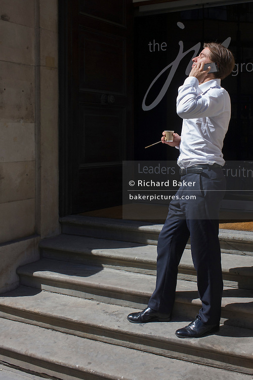 Young City businessman holds a conversation in warm sunshine outside an office building.