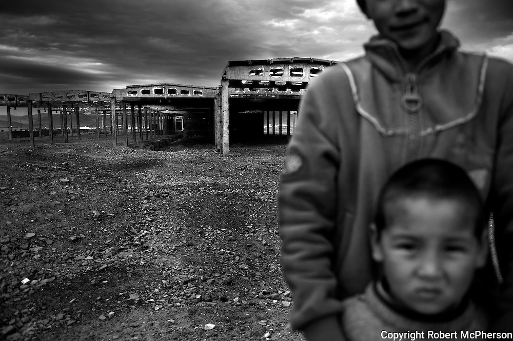 Mongolia(2008). Kazakh children infront of undeveloped industry from the Soviet era in Bayan Olgii...Bayan Ulgii town is located in Mongolia`s western-most province. It is set in the Altai mountains where Mongolia,China and Russia converge. It is the only province where Mongolians are not the majority: about 90% of the population are ethnically Kazakh and practise Islamic traditions. Bayan Ulgii town suffered from the collapse of the socialist system; artificially created plants and industries buckled. Suddenly, all services and goods became very expensive. Today, Bayan Ulgii is the poorest province of Mongolia. Maternal and infant mortality rate is much higher than in the rest of the country and the central hospital still use Soviet made equipment waiting to be replaced.