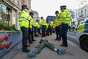 Police officers laid down a climate activist from Extinction Rebellion during the group's 'Impossible Rebellion' series of actions at Oxford Circus in central London, on Wednesday, August 25, 2021. - Climate change demonstrators from environmental activist group Extinction Rebellion continued with their latest round of protests in central London, promising two weeks of disruption. (VX Photo/ Vudi Xhymshiti)