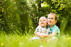 Two little brothers sitting in the garden