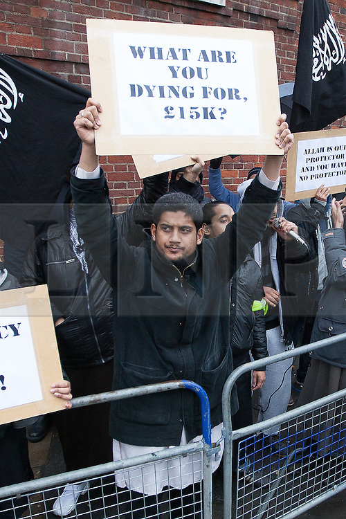"""© Licensed to London News Pictures . London , UK . SIDDHARTHA DHAR (C holding a sign that reads """" What are you dying for , £15k ? """") at a Muslims Against Crusades demonstration on Exhibition Road in London on the anniversary of Armistice Day , on November 11, 2010 . Dhar , also known as Abu Rumaysah , is to appear in a Channel 4 documentary , The Jihadis Next Door , this evening (19th January 2016) . It is believed Dhar in one of five executioners to have featured in a recent ISIS video , recorded in Syria . Photo credit : Joel Goodman/LNP"""