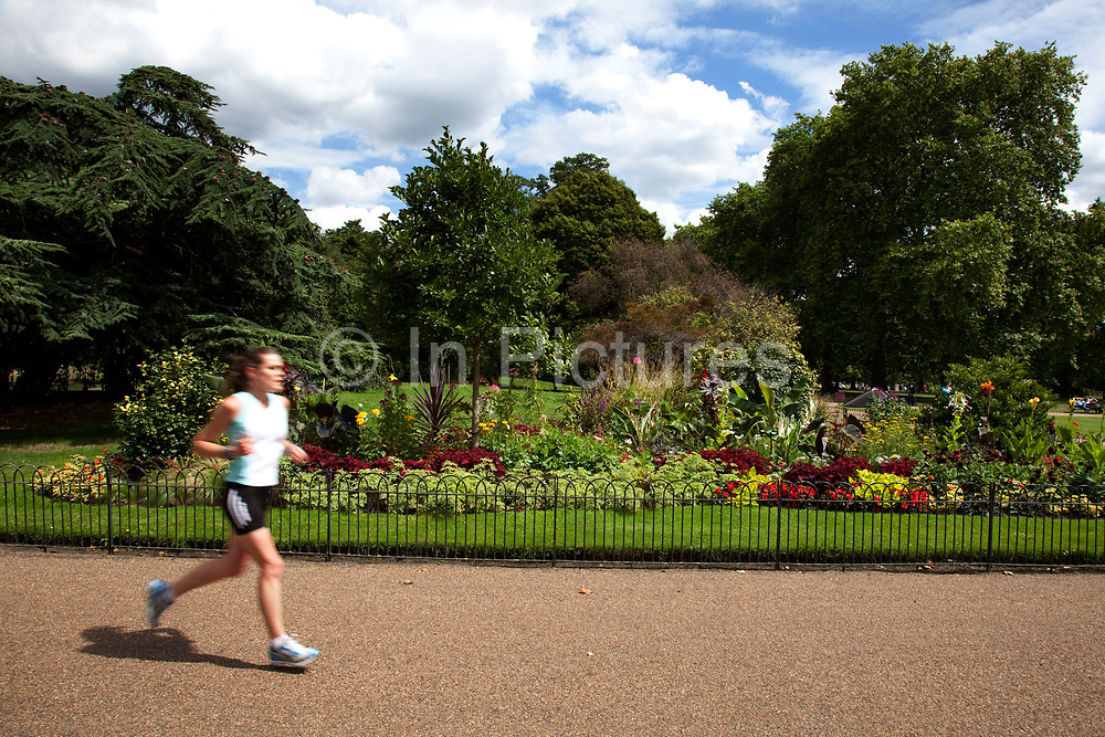 Woman out running for exercise in Hyde Park, Knightsbridge, West London.