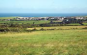 Linear coastal village of Trefin, viewed over fields, Pembrokeshire, Wales