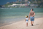 An adult and child look to the ocean while walking along the beach in Hawaii.