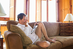 man at home in his underwear looking at an iPad