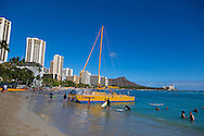 Waikiki Beach, the beachfront neighborhood in Honolulu on the south shore of the island of Oahu, Hawaii, USA.  Waikiki means Spouting Fresh Water in Hawaiian, named so because of the freshwater springs that were here when this area was marshland.  Now, it is famous for surfing, swimming and shopping.  Approximately eight million visitors from all over the world come to visit Waikiki Beach every year.