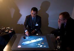 "A Microsoft representative demonstrates a $10,000 coffee table PC, the Surface. It features touchscreen technology that can sense and process multiple touches at the same time and ""turns an ordinary tabletop into a vibrant interactive surface."" It's intended for enhancing customer experiences inside retail stores -- or perhaps creating some really cool bar games. At the moment the Surface is available only to select partners in the United States, although Microsoft was gauging a possible entry into the European market. (Photo © Jock Fistick)"