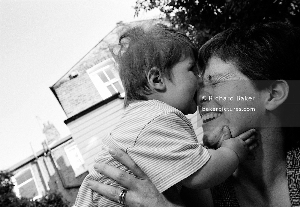 """More than you can chew."" A ten month-old infant uses new teeth to bite her mother's nose in the back garden of their Victorian south London terrace home. The mum winces in pain as the child sinks her new milk teeth into her skin but they enjoy a warm summer afternoon, playfully interacting with each other in a moment of parental love and harmony. The girl wears a short-sleeved t-shirt and has plump arms of baby fat, a healthy sign of a contented infant. This is from a documentary series of pictures about the first year of the photographer's first child Ella. Accompanied by personal reflections and references from various nursery rhymes, this work describes his wife Lynda's journey from expectant to actual motherhood and for Ella - from new-born to one year-old."
