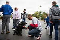 Lucky Jr receives birthday greetings from his visitors as well as a treat from Shane Kaplan during a birthday celebration in his honor at Sanborn's Auto on Saturday.  (Karen Bobotas/for the Laconia Daily Sun)