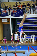 Young Australian gymnast competing on the uneven bars at the Prime 18th Annual Invitational Gymnastics Competition (Singapore, 2009), with Australian flag in background. Singapore