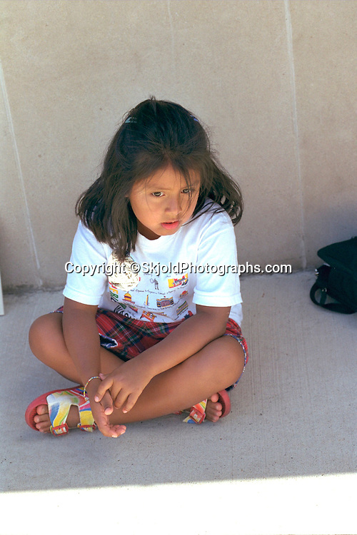 Pensive girl age 6 with legs crossed sitting on sidewalk.  Sault Ste. Marie  Michigan USA
