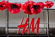 "Remembrance poppies hang in front of a branch of Swedish fashion chain H&M (Hennes & Mauritz AB) on the second day of England's second coronavirus lockdown on 6 November 2020 in Windsor, United Kingdom. Only retailers selling ""essential"" goods and services are permitted to remain open to the public during the second lockdown provided that they follow coronavirus guidelines and make their premises COVID-19 secure."
