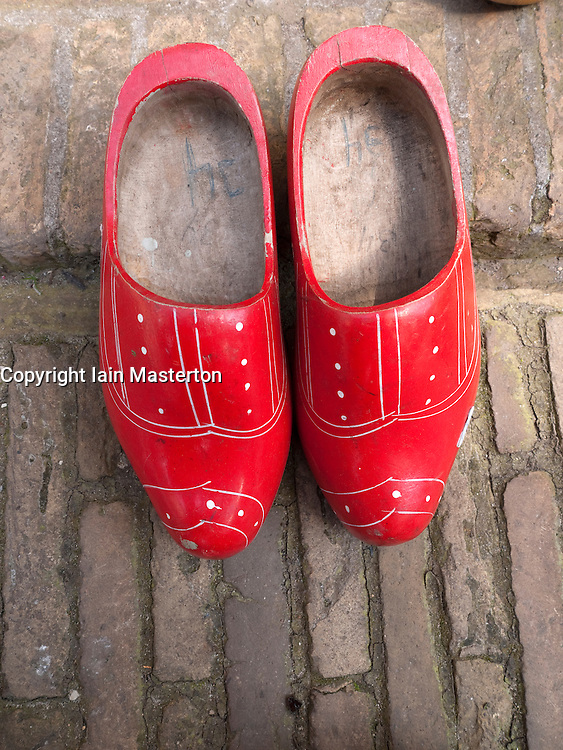 Old red wooden dutch clogs outside house in The Netherlands