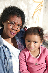 Elderly grandmother sitting on a bench in the sunshine with her granddaughter,