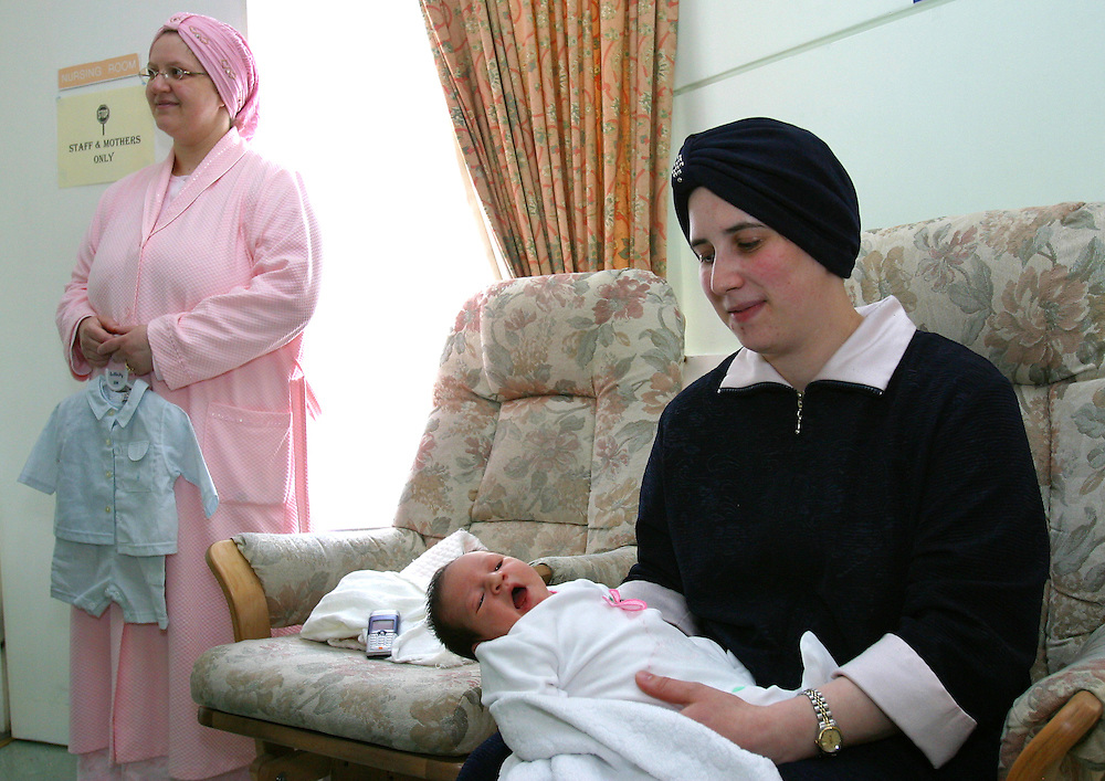 A 28 year-old Orthodox Jewish mother shows off her 3 day-old baby. After having her child she is staying in Beis Brucha, a mother and baby home run by Agudas Israel Housing Association who assist mothers for a up to a week after childbirth with care. Stamford Hill, Hackney, London.