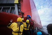Greenpeace activists board the cargo ship Elbe Highway September 21st 2017, Thames Estuary, Kent, United Kingdom. Greenpeace volunteers in kayaks, speed boats and climbers on the jetty prevent the 23,498-tonne cargo ship Elbe Highway from docking at Sheerness in Kent.  The cargo ship is bringing Volkswagen diesel cars into the UK and the Greenpeace action is to prevent this from happening and to make VW ditch diesel. Two climbers board the ship and hang a banner on the roll-on roll-off part of the ship preventing any cars from being off-loaded. The action is part of a long running Greenpeace campaign to curb diesel emmissions and air pollution broght on by diesel cars.