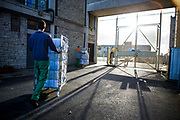 Prisoners escorted by officers  move washing from the industrial laundry in HMP/YOI Portland, a resettlement prison with a capacity for 530 prisoners. Dorset, United Kingdom.