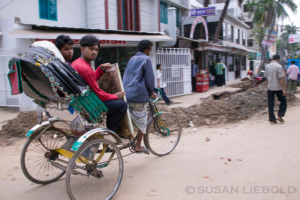 Jalal, a rickshaw puller, with two customers.